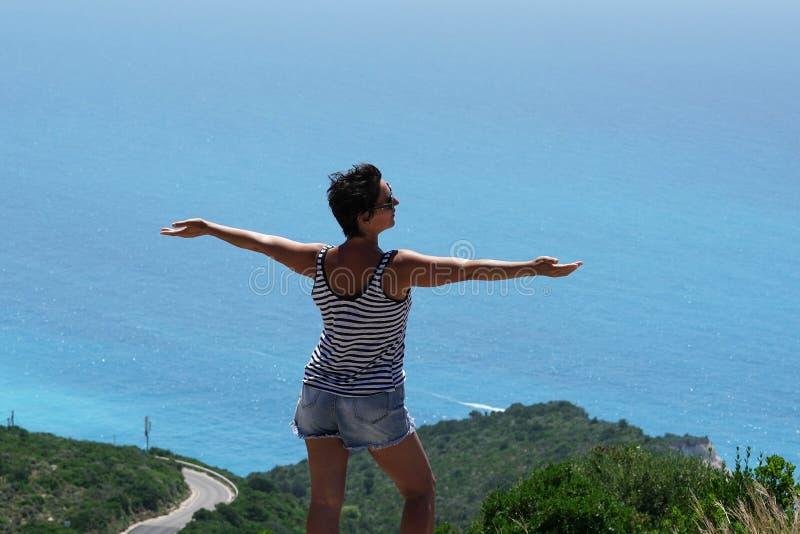 Un turista disfruta de la vista espléndida del panorama de Oporto Katsiki en Lefkada fotografía de archivo libre de regalías