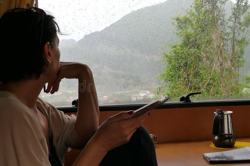 Un turista esamina il paesaggio come cadute della pioggia mentre su una festa del motorhome fotografia stock
