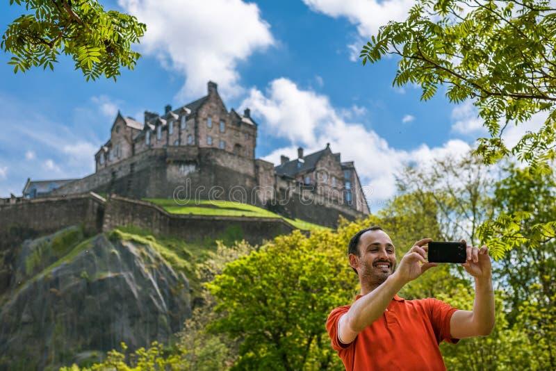 Un turista felice del giovane al castello di Edimburgo che prende selfie sulla m. fotografia stock libera da diritti