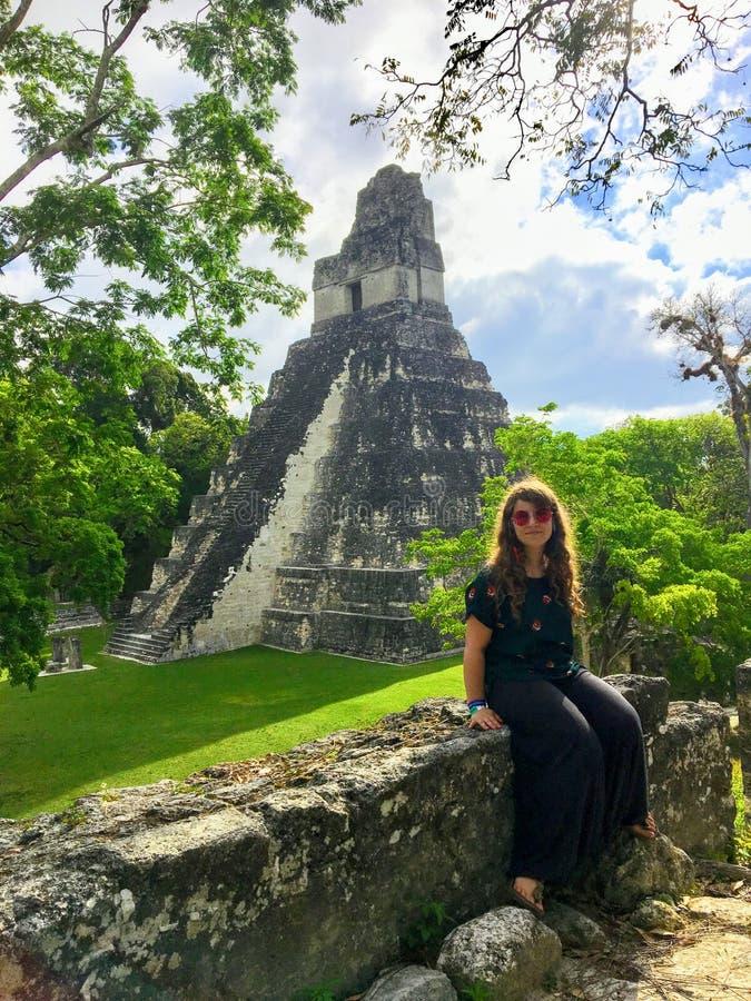 Un turista femenino joven bonito que presenta delante de las ruinas de Tikal, ruinas mayas antiguas profundamente en selvas tropi imagen de archivo libre de regalías