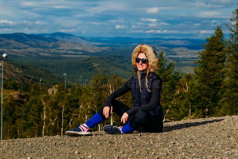 Un turista femenino sonriente joven en las montañas se sienta en la tierra fotos de archivo libres de regalías