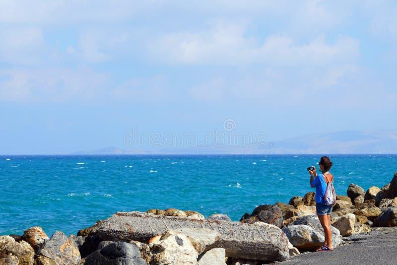 Un turista fotograf?a el mar en Creta foto de archivo libre de regalías