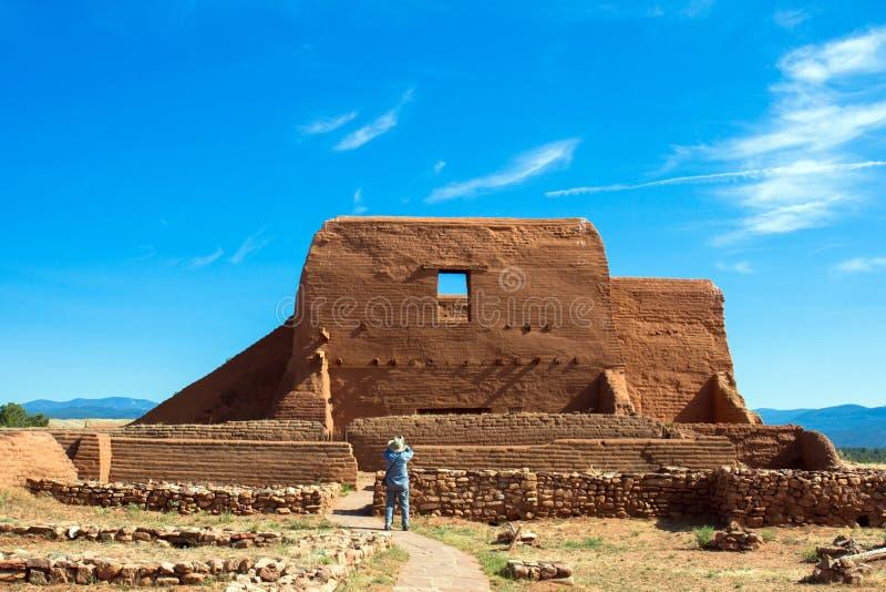 Un turista fotografa la chiesa storica di missione nel parco storico nazionale dei PECO nel New Mexico del Nord immagini stock libere da diritti
