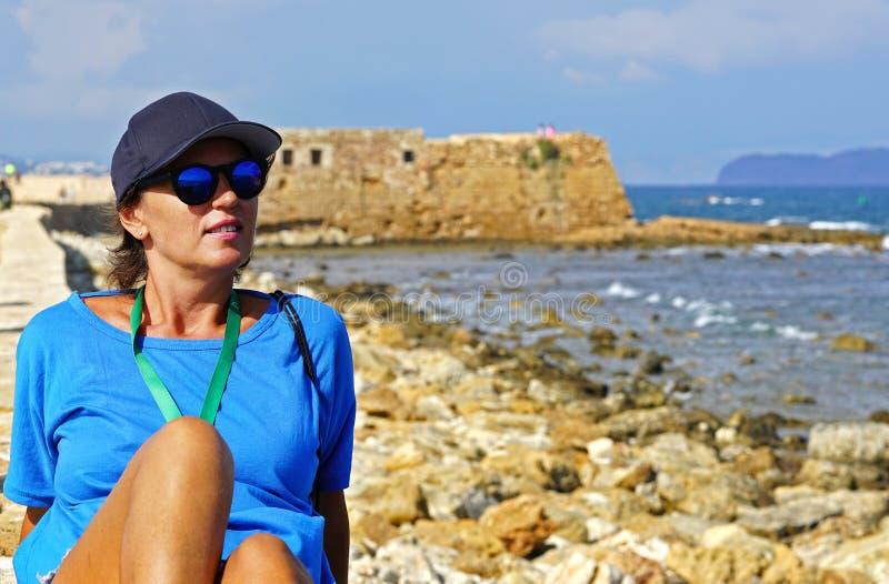Un turista gode di bello giorno soleggiato di ottobre che ammira la vecchia città dalle pareti del porto, Xania, Creta immagine stock libera da diritti