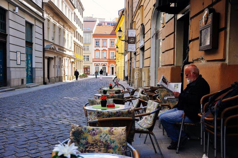Un turista goza de un periódico en Bratislava vieja, Eslovaquia fotos de archivo
