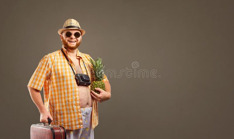 Un turista grasso divertente con una borsa sorride fotografia stock