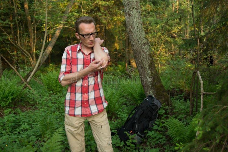 Un turista ha perso nel legno che combatte le zanzare fotografie stock