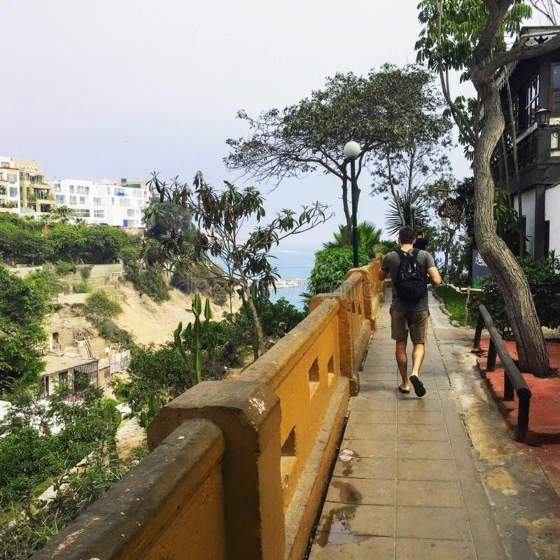 Un turista masculino joven que camina a lo largo de un patio con los restaurantes arriba fotografía de archivo libre de regalías