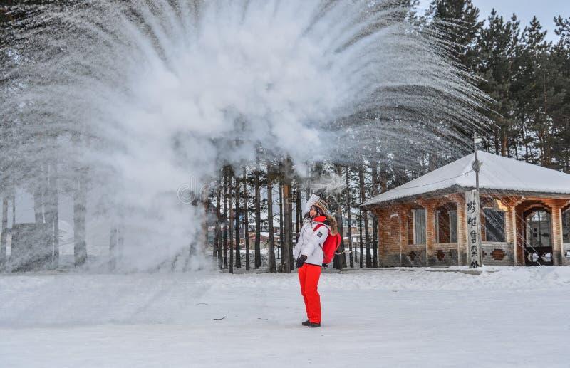 Un turista que lanza la agua caliente en el parque del invierno imagen de archivo libre de regalías