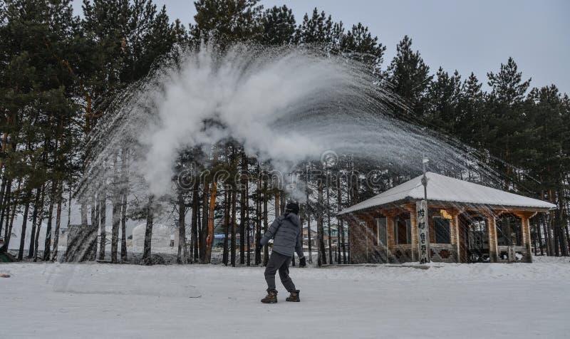 Un turista que lanza la agua caliente en el parque del invierno fotos de archivo