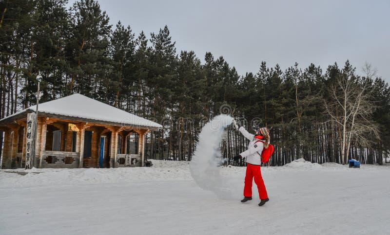 Un turista que lanza la agua caliente en el parque del invierno imagenes de archivo