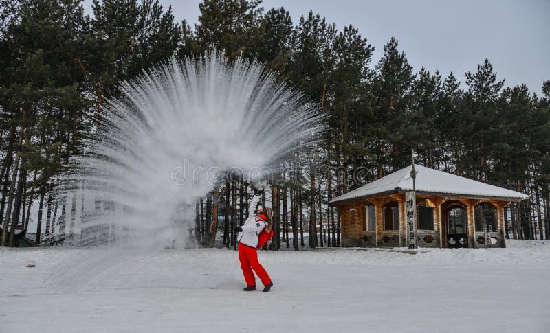 Un turista que lanza la agua caliente en el parque del invierno fotografía de archivo