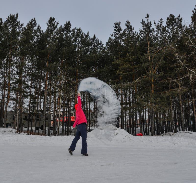 Un turista que lanza la agua caliente en el parque del invierno foto de archivo