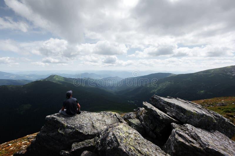 Un turista solitario que se sienta al borde del acantilado imagenes de archivo