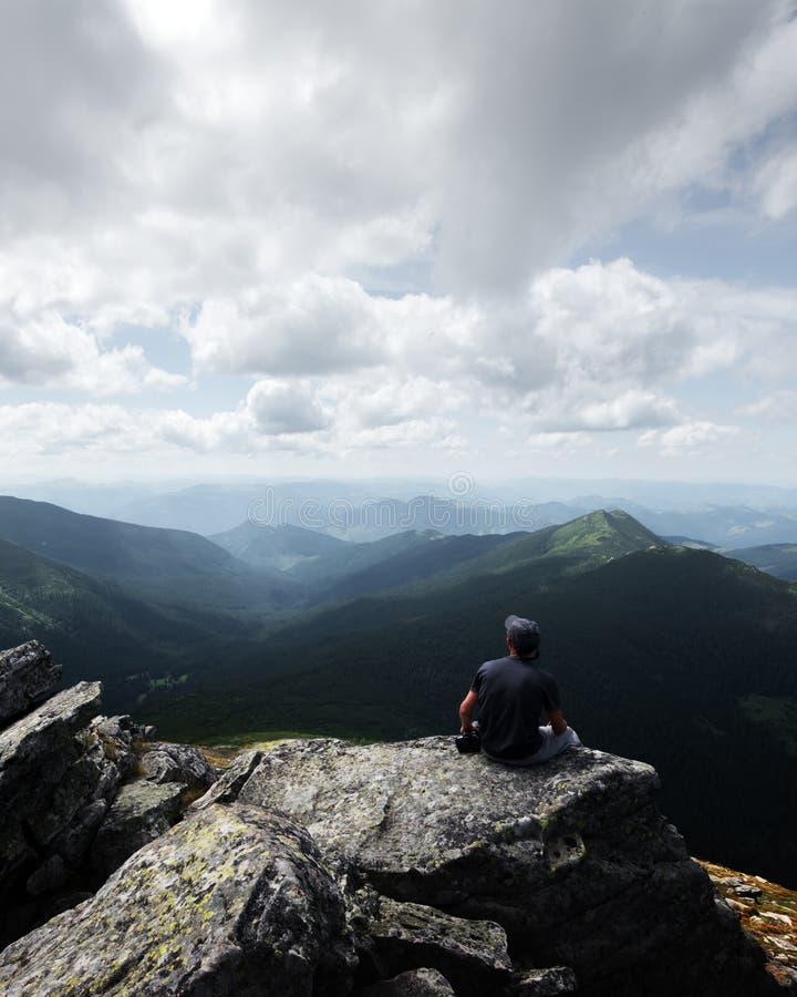 Un turista solitario que se sienta al borde del acantilado fotos de archivo