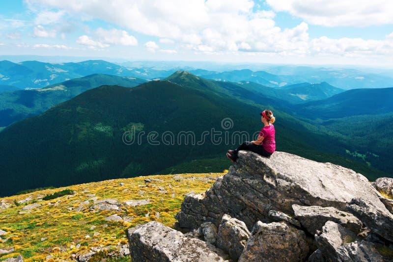 Un turista solitario que se sienta al borde del acantilado foto de archivo