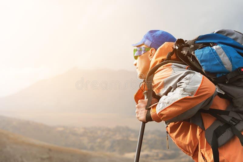 Un turista solo gode delle viste su nelle montagne in cui non c'è erba del villaggio e della neve immagini stock libere da diritti