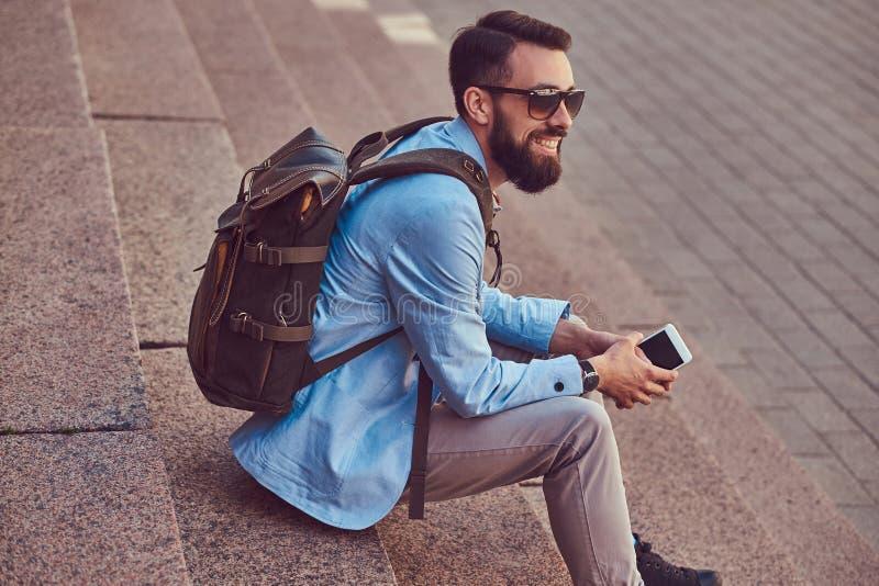 Un turista sorridente con una barba folta e un taglio di capelli, abbigliamento casual d'uso e uno zaino, tiene uno smartphone, s immagini stock