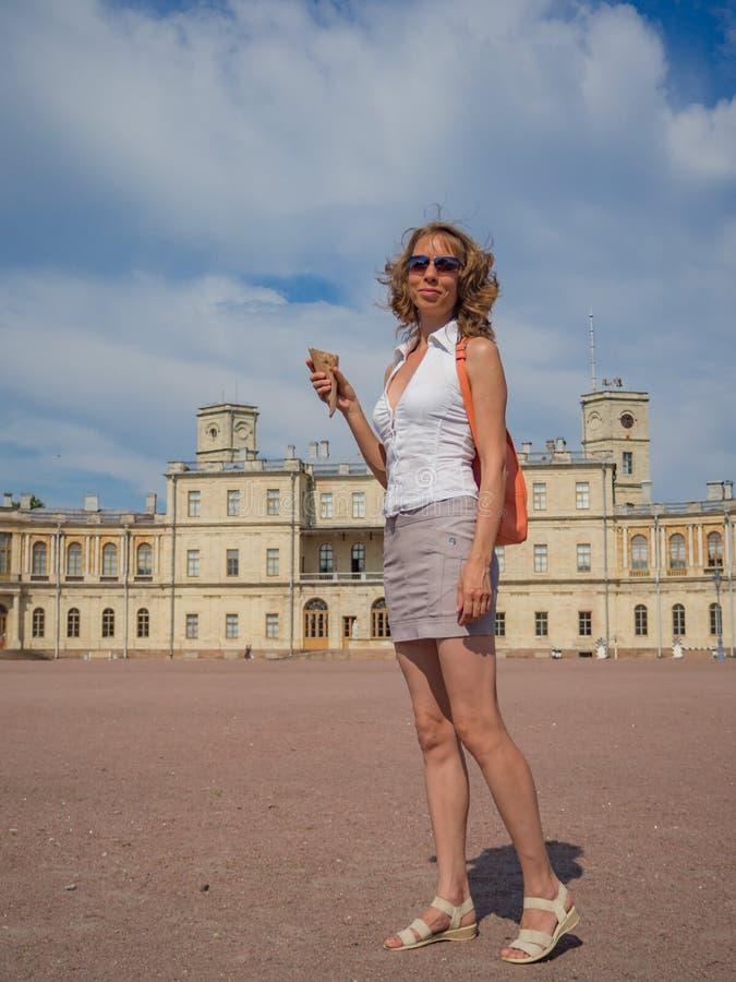 Un turista sorridente della donna con il piccolo zaino arancio nel centro di Gatcina Turismo in Europa, turista della donna al pa fotografia stock libera da diritti