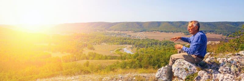 Un turista sta sopra una montagna ed ammira da sopra una vista del taiga di Ural immagini stock