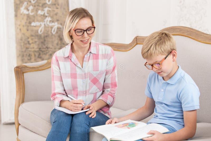 Un tutor bello e il suo giovane alunno che fanno i compiti in inglese Un ragazzino che traduce il testo nel suo libro di testo me immagini stock