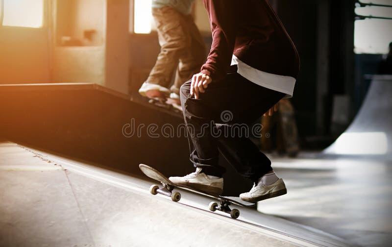Un type à la mode habillé monte une planche à roulettes sur une rampe et va faire un saut photographie stock