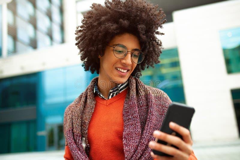 Un type aux cheveux bouclés beau de métis est habillé dans une écharpe de style de la jeunesse à la mode et le chandail écrit un  photos libres de droits