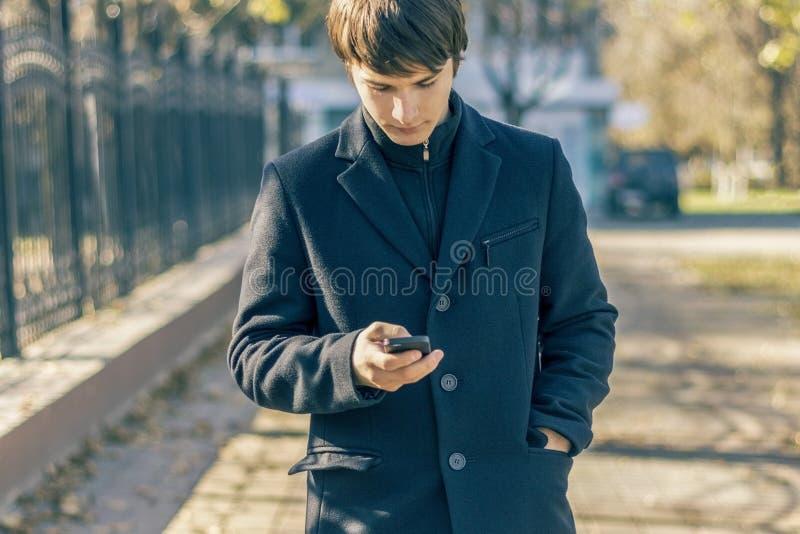 Un type dans un manteau noir avec un téléphone portable dans ses promenades de main en parc d'automne Montre dans votre mobile images libres de droits