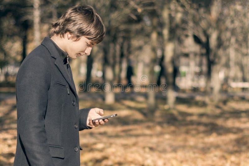 Un type dans un manteau noir avec un téléphone portable dans ses promenades de main en parc d'automne Montre dans votre mobile photos stock