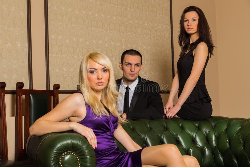 Un type et deux filles dans la chambre image stock