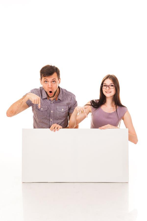 Un type et une fille posent avec un signe blanc, carton, un connexion leurs mains photo libre de droits