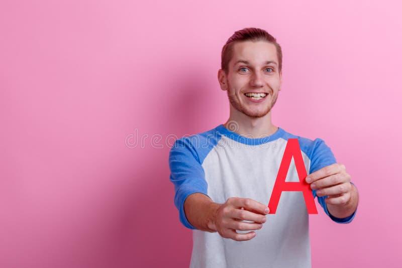 Un type gai tenant A à marquer d'une pierre blanche Fond rose images stock