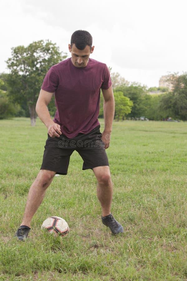 Un type jouant au football dans l'équipement professionnel au stade photographie stock