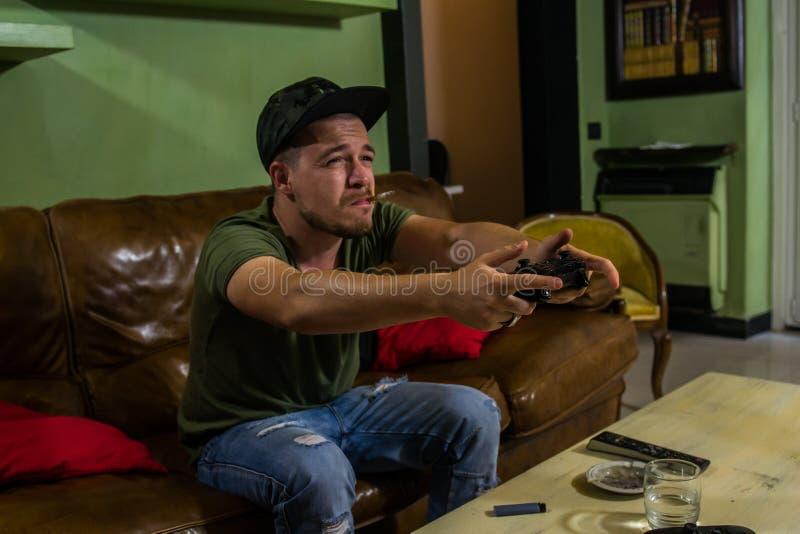 Un type joue très intensivelly un jeu vidéo et fume dans le même temps photographie stock libre de droits