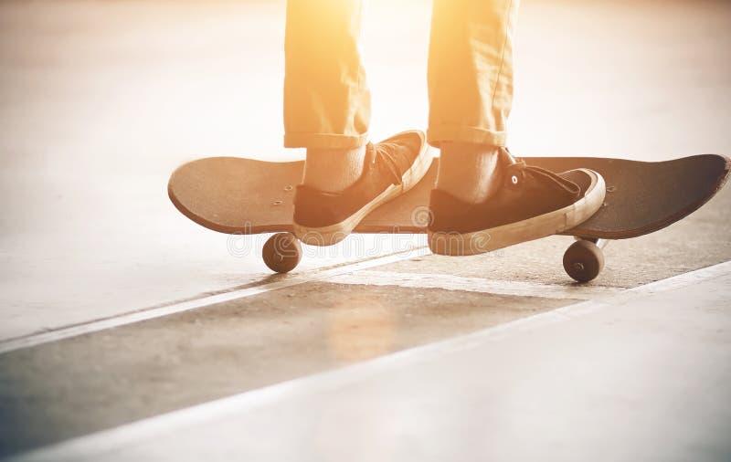 Un type monte sur l'asphalte et allume une planche à roulettes photographie stock libre de droits