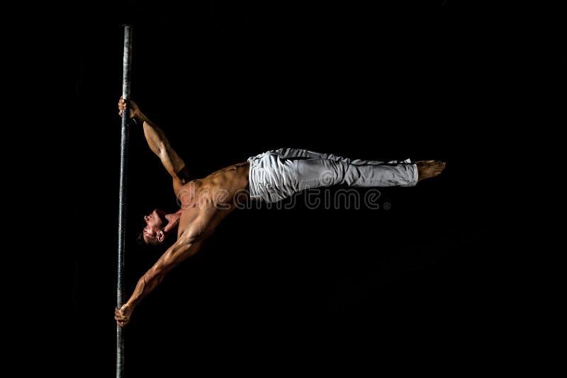 Un type musculaire fort habillé dans le pantalon blanc exécute un tour sur un poteau dedans sur un fond noir photo libre de droits