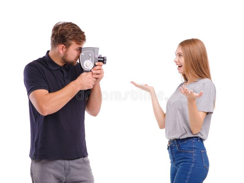 Un type prend une photo d'une fille sur un rétro appareil-photo D'isolement sur le fond blanc photographie stock libre de droits