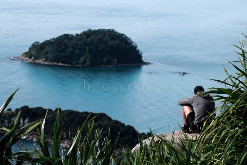 Un type s'asseyant au bord d'une falaise photographie stock libre de droits