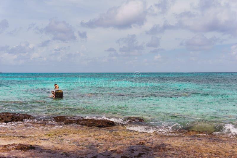 Un type s'asseyant sur la plage photo libre de droits