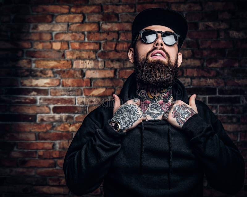 Un type tatoué élégant dans un hoodie noir et des lunettes de soleil Photo de studio contre le mur de briques photo libre de droits