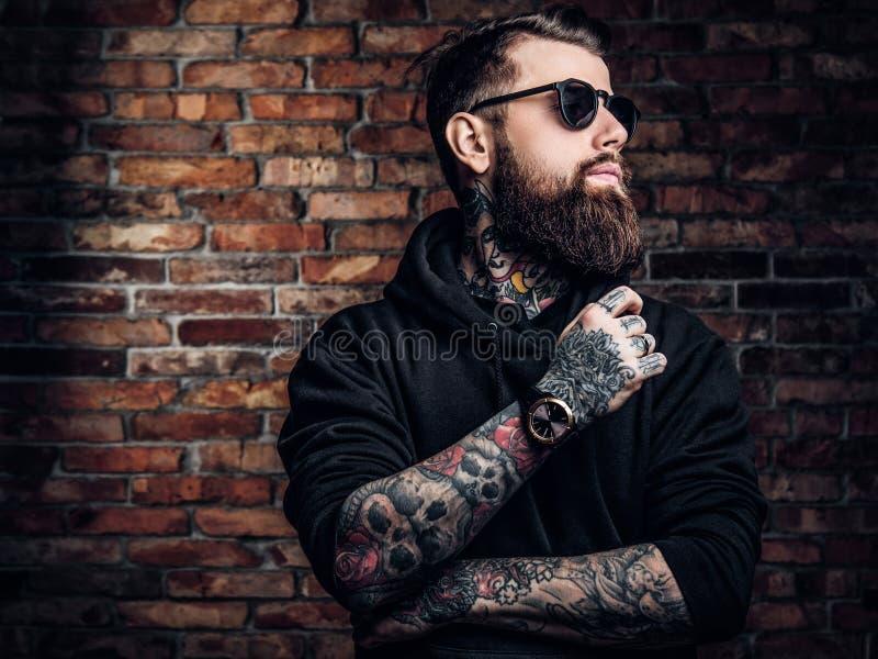 Un type tatoué élégant dans un hoodie noir et des lunettes de soleil Photo de studio contre le mur de briques photographie stock libre de droits