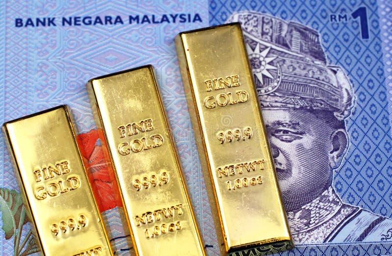 Un'una banconota malese di ringgit con tre lingotti dell'oro immagine stock