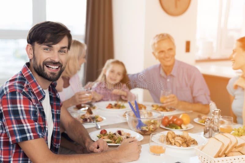Un uomo è sorridente e posante la seduta ad una tavola festiva il giorno di ringraziamento Contro lo sfondo della sua famiglia immagini stock