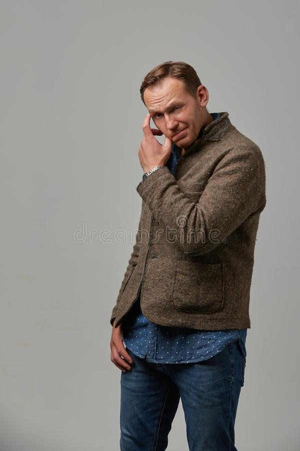 Un uomo in abbigliamento casuale nasconde il suo fronte con le sue mani su un fondo grigio Fronte emozionale e coraggioso Isolato fotografia stock