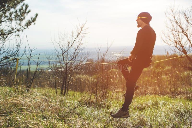 Un uomo all'età della seduta in vetri con un cappello e le scarpe da tennis sullo slackline, fermi equilibra e gode della vita su fotografia stock