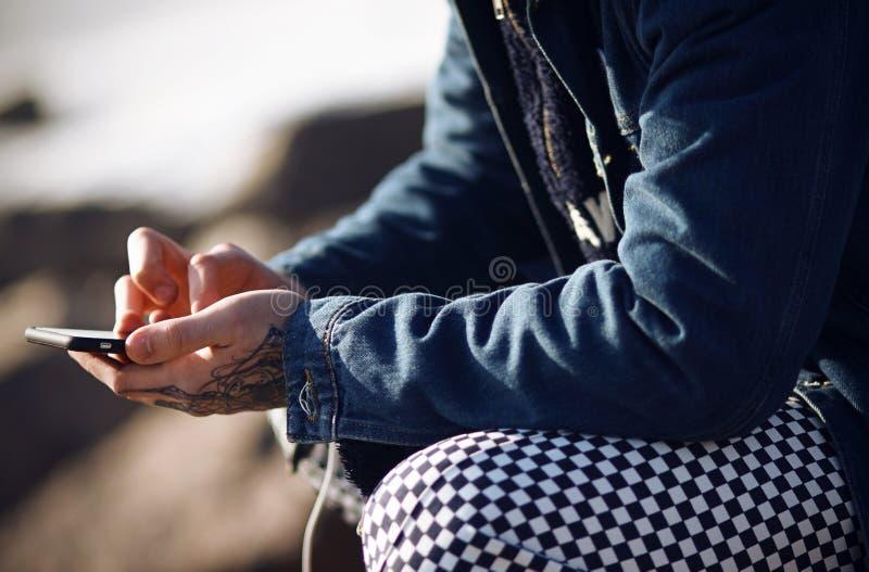Un uomo alla moda vestito tiene un telefono di tocco immagini stock