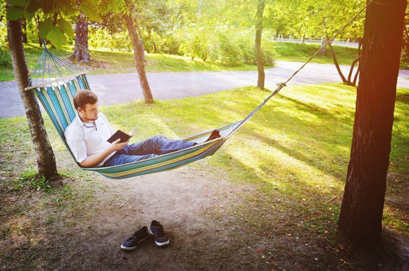 Un uomo in amaca legge un libro immagine stock