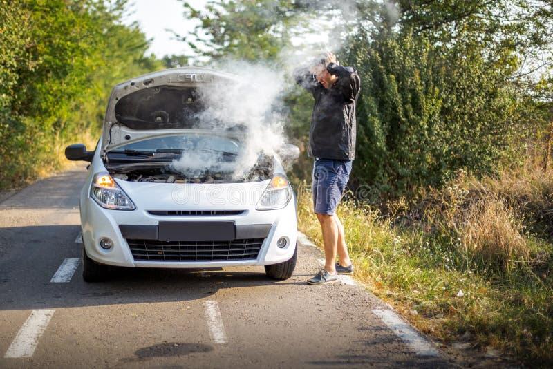 Un uomo ansioso vicino ad un'automobile rotta sulla strada fotografie stock