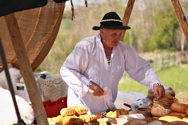 Un uomo anziano in abbigliamento tradizionale vende i formaggi ad un mercato di strada fotografia stock