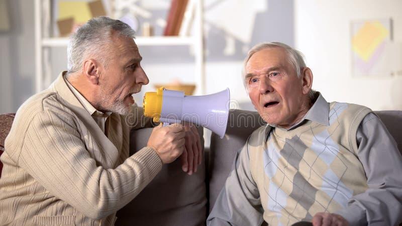 Un uomo anziano che parla in megafono a un vecchio amico sordo, problemi di salute, primo piano fotografia stock